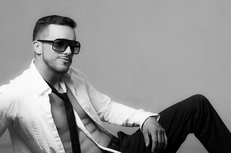 shirt unbuttoned: Sexy young male model wearing sunglasses sitting with unbuttoned shirt black and white portrait