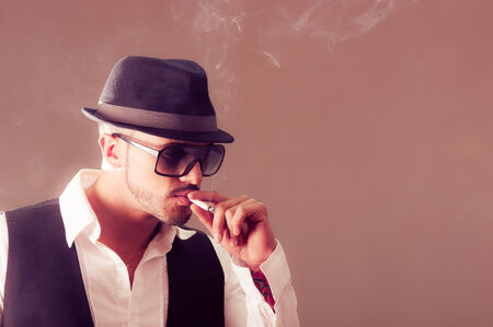 Young handsome stylish male model wearing a hat smoking a cigarette photo