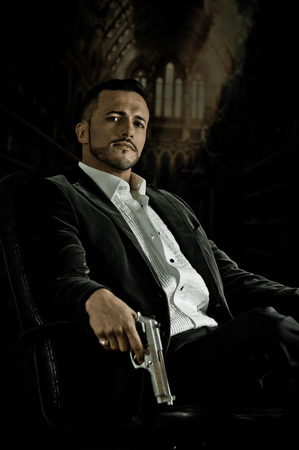 Stylish hispanic young handsome man model mobster spy hitman killer sitting in a chair holding a gun over dark background Archivio Fotografico