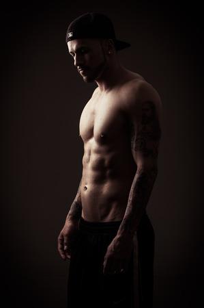 modelos masculinos: Modelo masculino muscular atlético descamisado con gorra vista lateral posando en tonos de color