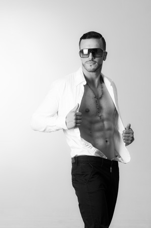 open shirt: black and white portrait of handsome young male model posing holding his unbuttoned shirt