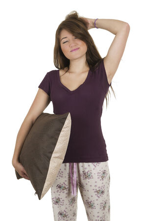 wellness sleepy: Beautiful young teenage brunette girl in pajamas holding a pillow looking sleepy isolated on white