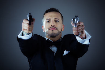 Sexy man gangster agent criminal police in a tuxedo pointing two guns photo