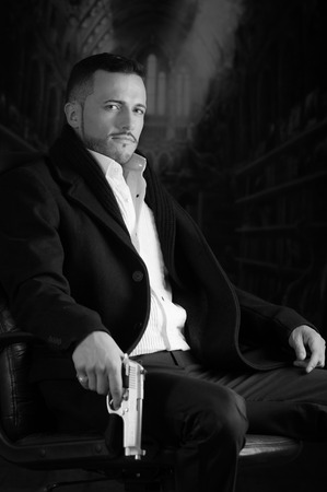 Sophisticated young man agent police killer hitman assassin sitting in a chair holding a gun over dark background black and white portrait photo