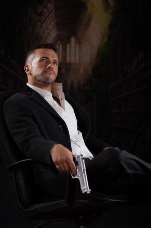 sicario: Elegante joven hispano modelo hombre guapo esp�a asesino mafioso asesino a sueldo mirando sentado en una silla con una pistola sobre fondo oscuro