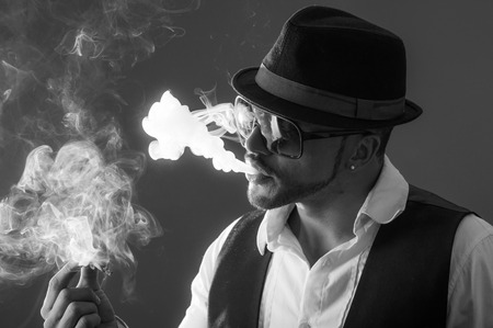 Young handsome elegant stylish male model wearing sunglasses and hat smoking a cigarette black and white portrait photo