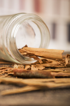 cannelle: closeup cinnamon sticks in a jar on wooden table selective focus