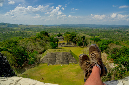 mans shoes overlooking xunantunich maya site ruins in belize caribbean photo