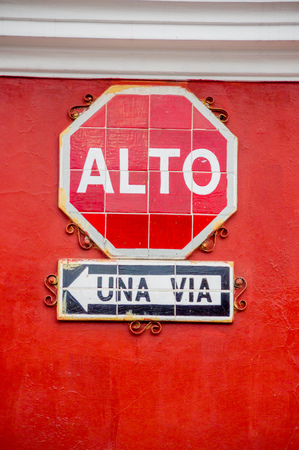 one lane road sign: stop and one way street signs in spanish alto una via hanging on red wall