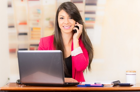 Beautiful young brunette girl student businesswoman professional using cell phone working with laptop photo