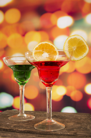 red and green cocktails with lemon slice on a wooden table with party lights in the background photo