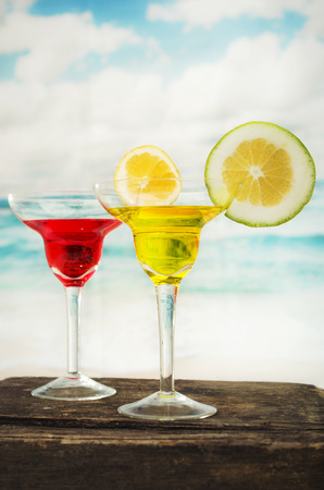 two tropical fruity cocktails red yellow on wooden table with the sea beach ocean in the background  photo