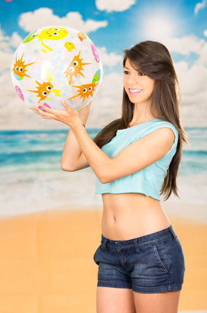beautiful young teenage girl playing with beach ball in the beach summer photo