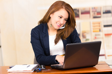 Beautiful young smiling girl working behind a desk with laptop talking on cell phone photo