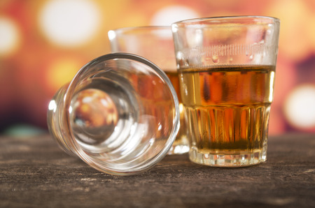 glass of rum whiskey alcohol on wooden table over defocused lights background photo