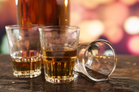three glasses of rum whiskey alcohol on wooden table over defocused lights background photo