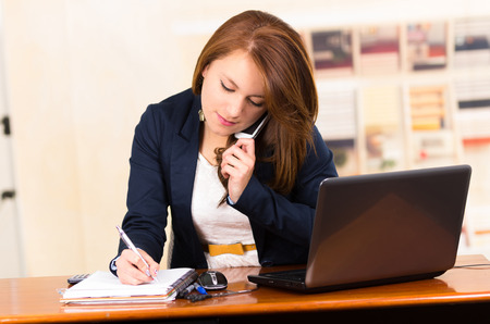 portrait of beautiful young secretary working from desk talking on cell phone Standard-Bild