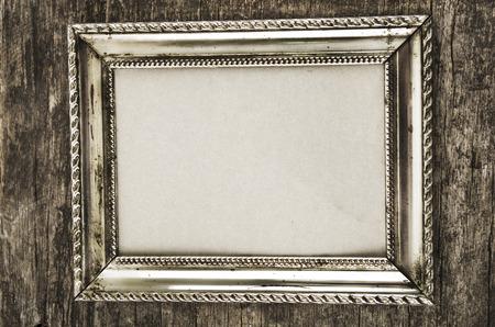 old metallic silver photo frame on wooden background photo