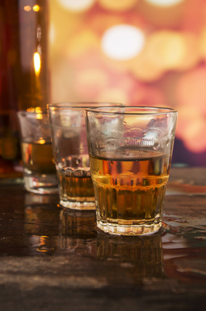 amaretto: bottle and three glasses of rum whiskey alcohol on wooden table over defocused lights background Stock Photo