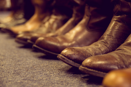 cowboy boots: brown vintage leather boots aligned selective focus Stock Photo