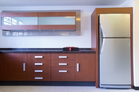 woden: modern kitchen display with silver refrigerator and woden cabinets
