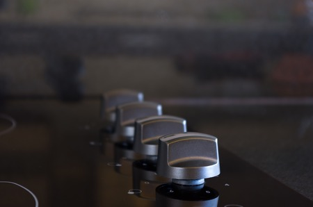 closeup shot of elegant and black stove knobs photo
