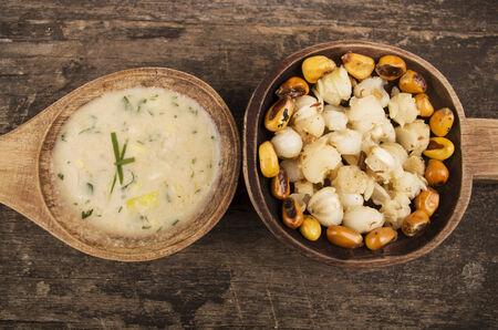 sémola de maíz y nueces de maíz tostado Mote con una salsa de ají tostado en cucharas de madera de comida tradicional ecuatoriana Foto de archivo