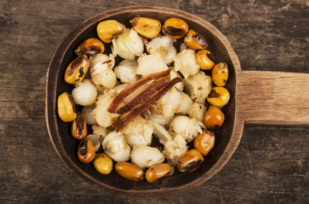 mote: hominy and toasted corn nuts mote with tostado on wooden spoon ecuadorian traditional food