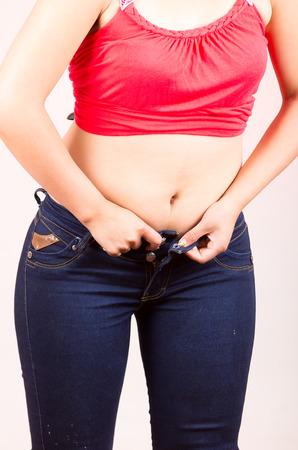 jeune fille luttent essayer d'adapter dans des jeans serrés incapables de bouton Banque d'images