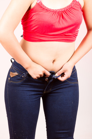 women in jeans: young girl struggling trying to fit into tight jeans unable to button Stock Photo
