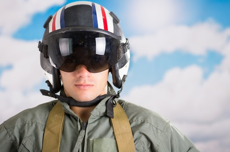 closeup portrait of young pilot wearing helmet with a sky background