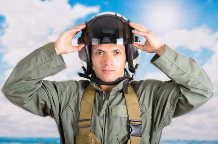 fighter pilot: closeup portrait of young pilot holding helmet with a sky background