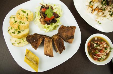 mote: fritada fried pork agrio sauce and mote traditional food from Ecuador