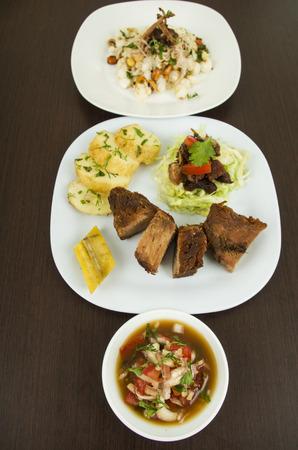 ecuadorian: fritada with mote con chicharron fried pork hominy toasted corn nuts Ecuadorian typical food