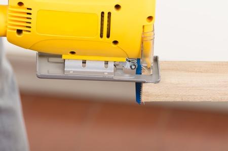 close up electric jigsaw tool cutting wood photo