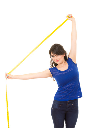 pretty young girl holding measuring tape with her arms extended above her isolated on white photo