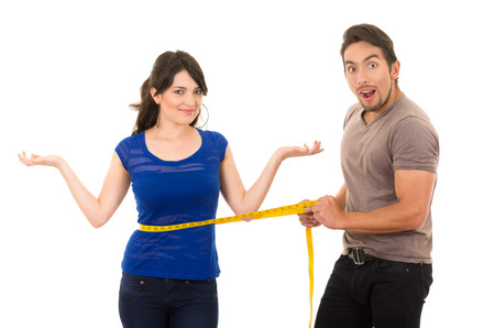 slimming: handsome open mouthed man holding measuring tape around thin fit young girls stomach concept of dieting fitness weightloss  isolated on white