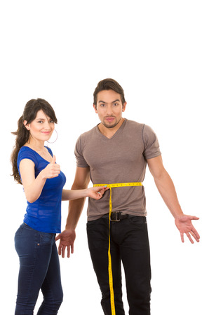 beautiful content girl holding measuing tape around handsome muscular mans fit stomach concept of dieting fitness weightloss