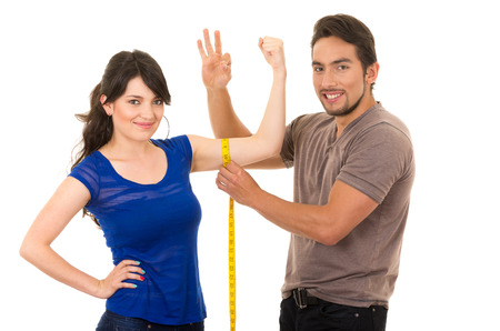handsome man holding measuring tape around thin fit young girls arm isolated on white photo