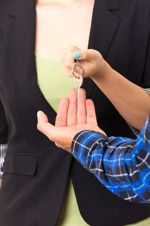 closeup hands handing over key concept of sale buyer isolated on white photo