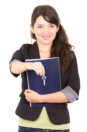 portrait of beautiful woman  real estate agent holding a key isolated on white photo