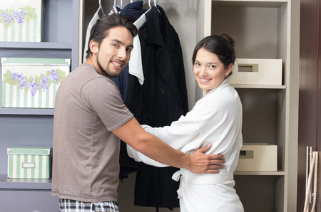 married young happt couple posing hugging in the closet photo