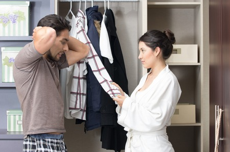 married young couple choosing arguing about clothes in the closet photo