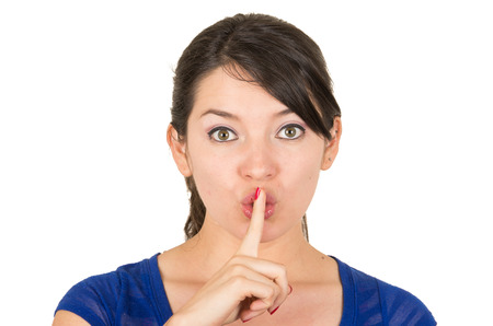 shhh: closeup of beautiful young woman gesturing silence shhh with finger on mouth isolated on white