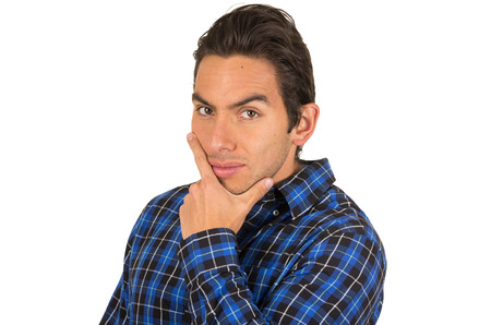 handsome young flirty latin man wearing a blue plaid shirt posing with hand on chin isolated on white Stock Photo