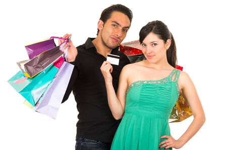 happy young woman holding credit card while boyfriend husband carries shopping bags isolated on white
