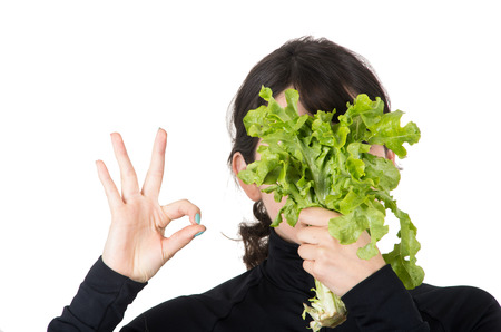 all right: closeup portrait of young girl holding fresh lettuce leaves in front of her face gesturing all right isolated on white Stock Photo