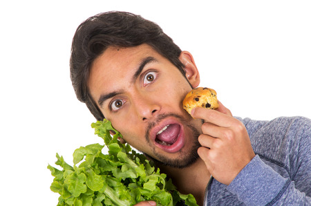 mouthed: closeup portrait of confused handsome young man holding fresh lettuce leaves and a muffin isolated on white