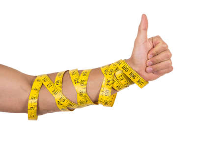 man's thumb: mans arm wrapped in measuring tape holding thumb up concept of healthy diet isolated on white Stock Photo