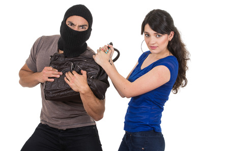 masked male thief robbing beautiful young girl with hand bag isolated on white photo